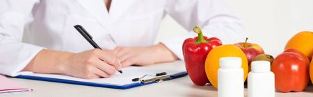 Photo pour panoramic shot of dietitian in white coat writing in clipboard at workplace with pills, fruits and vegetables on table - image libre de droit