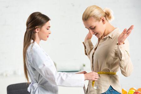 Photo pour side view of dietitian in white coat measuring waist for patient - image libre de droit