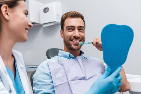 selective focus of happy man brushing teeth near attractive dentist holding mirror