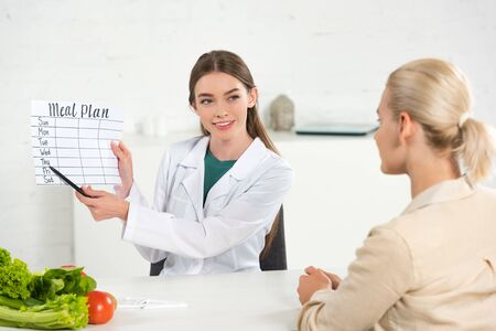Photo pour smiling dietitian in white coat holding meal plan and patient at table - image libre de droit