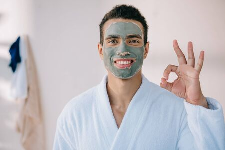 Photo pour handsome man with face mask and in bathrobe showing okay sign and looking at camera - image libre de droit