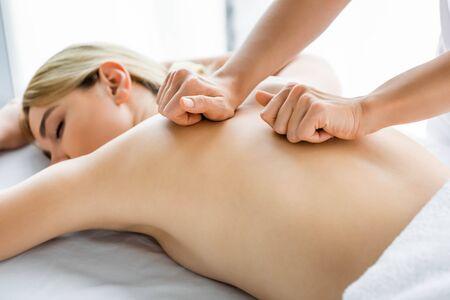 Foto de cropped view of masseur doing back massage to woman in spa  - Imagen libre de derechos