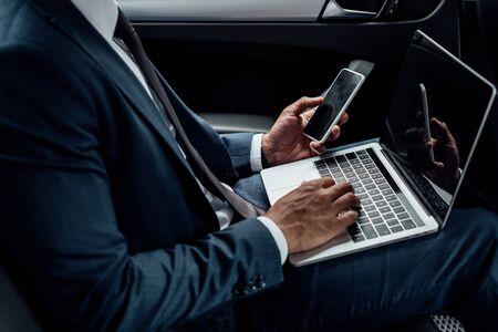 Foto de cropped view of african american businessman using laptop and smartphone in car - Imagen libre de derechos