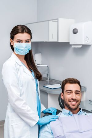 dentist in medical mask and latex gloves standing near happy patient