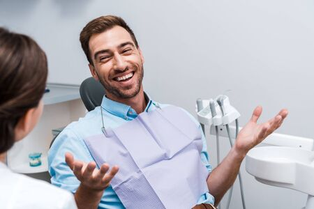 selective focus of happy patient gesturing and looking at dentist