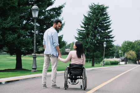 Photo pour back view of young disabled woman holding hands with handsome boyfriend while walking in park together - image libre de droit