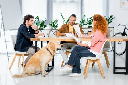 Photo pour three friends sitting at table and doing paperwork in office - image libre de droit