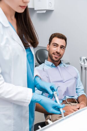 selective focus of cheerful man looking at dentist in clinic