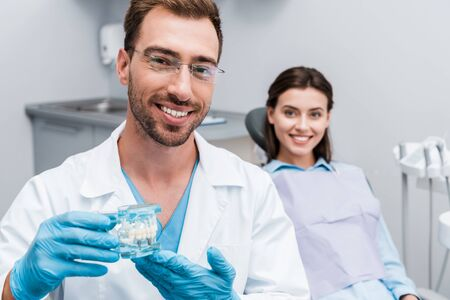 selective focus of happy bearded dentist holding teeth model near happy girl