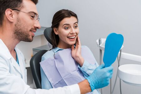 selective focus of happy woman looking at mirror near handsome dentist
