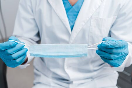 Foto de cropped view of man in blue latex gloves holding medical mask - Imagen libre de derechos