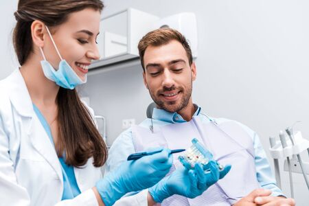 selective focus of attractive dentist in latex gloves holding pen near teeth model and happy patient