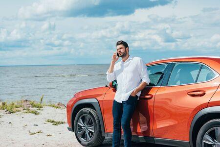 Foto de handsome man in white shirt talking on smartphone outside - Imagen libre de derechos