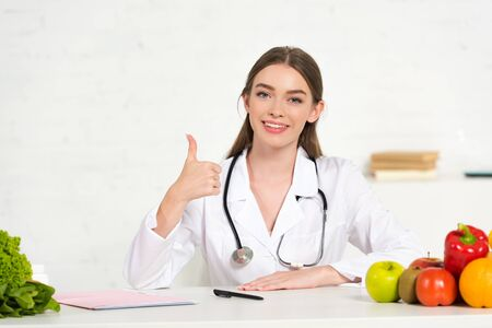 Photo pour front view of smiling dietitian in white coat with stethoscope showing thumb up at workplace with fruits and vegetables on table - image libre de droit