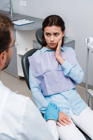 selective focus of upset woman touching face and looking at dentist
