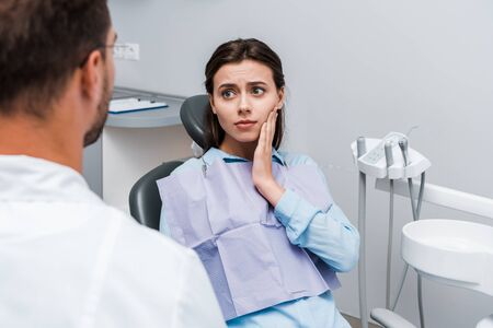 selective focus of attractive and sad woman having toothache and looking at dentist