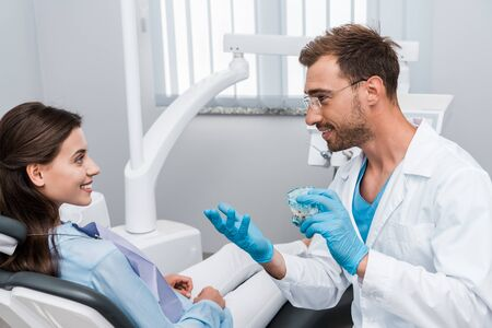 cheerful dentist in glasses holding tooth model and looking at happy woman