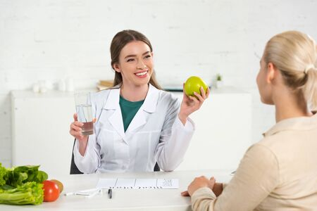 Photo pour smiling dietitian in white coat holding apple and glass of water and patient at table - image libre de droit