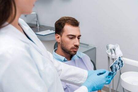selective focus of man looking at x-ray near dentist in white coat