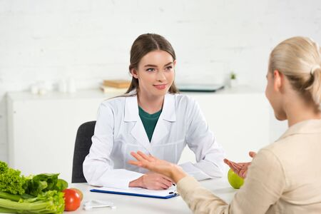 Photo pour smiling dietitian in white coat looking at patient at table - image libre de droit