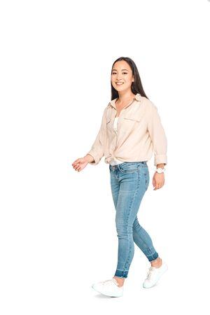 Foto de attractive asian woman in blue jeans looking at camera while walking on white background - Imagen libre de derechos