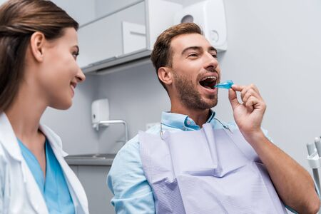 selective focus of patient putting retainer in mouth near happy dentist