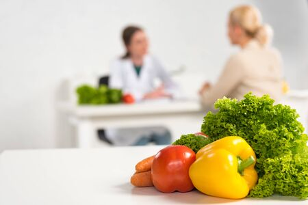 Photo pour selective focus of dietitian in white coat and patient at table and fresh vegetables on foreground - image libre de droit