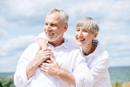 Photo pour happy senior couple in white shirts embracing under blue sky - image libre de droit