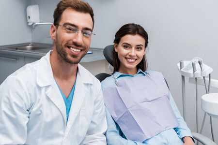 selective focus of happy and attractive girl smiling near handsome dentist in glasses