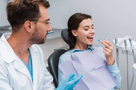 selective focus of cheerful woman looking at retainer near handsome dentist in glasses