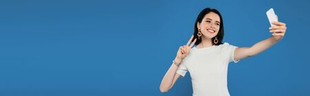 Photo for panoramic shot of smiling elegant woman in dress taking selfie and showing peace sign isolated on blue - Royalty Free Image