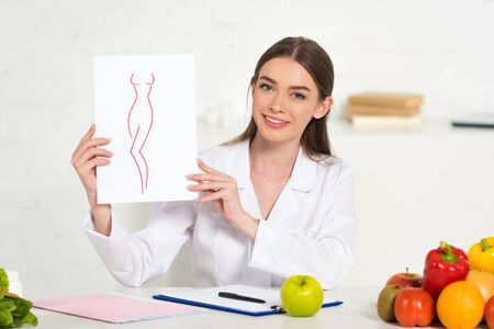 Photo pour smiling dietitian in white coat holding paper with image of perfect body at workplace with fruits and vegetables on table - image libre de droit