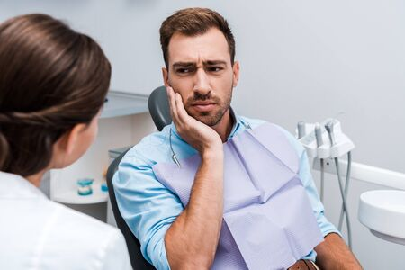 selective focus of upset patient touching face while having toothache near dentist