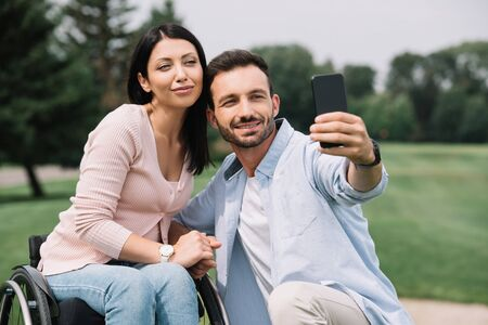 Photo pour happy man taking selfie on smartphone with smiling disabled girlfriend in park - image libre de droit