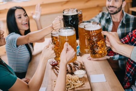 Foto de cheerful friends clinking mugs of beer while celebrating octoberfest in pub - Imagen libre de derechos