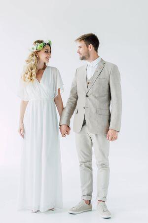 Foto de attractive bride and handsome bridegroom holding hands and looking at each other - Imagen libre de derechos