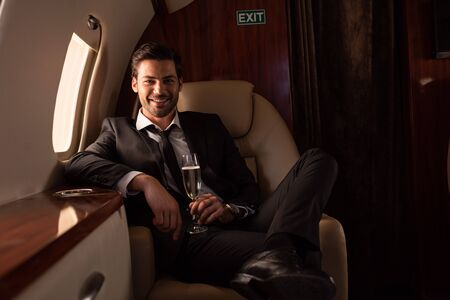 Photo pour handsome smiling man holding glass of champagne in plane - image libre de droit