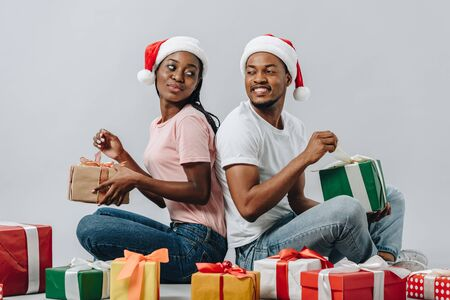 Photo for African American couple in Santa hat sitting back to back, opening presents and looking at each other isolated on grey - Royalty Free Image