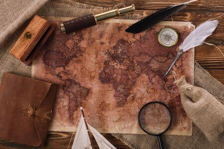 Foto de top view of old world map near telescope, nib and compass on wooden surface - Imagen libre de derechos