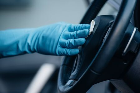 Photo pour cropped view of car cleaner in rubber glove wiping steering wheel  - image libre de droit