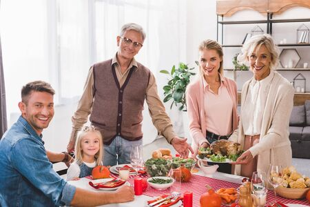 Photo pour family members sitting at table and holding plate with turkey in Thanksgiving day - image libre de droit