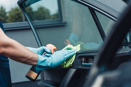 Photo for cropped view of car cleaner wiping car door with rag - Royalty Free Image