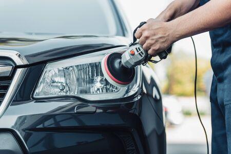 Photo pour cropped view of car cleaner polishing headlamp with polish machine - image libre de droit