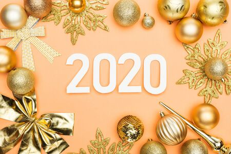 Foto de top view of white 2020 numbers in frame of golden christmas decoration on orange background - Imagen libre de derechos