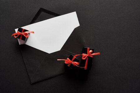 Foto de top view of black envelope with blank card near decorative gift boxes on black background - Imagen libre de derechos