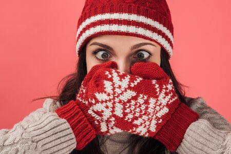 Photo pour woman in knitted hat covering face with warm gloves isolated on pink - image libre de droit