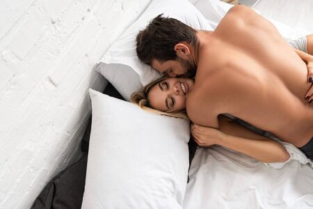 Photo for beautiful smiling couple hugging in bed in the morning - Royalty Free Image