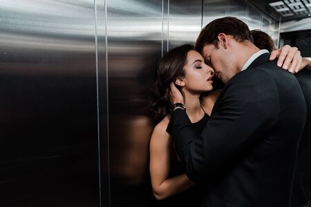 Photo for beautiful passionate couple hugging and going to kiss in lift - Royalty Free Image