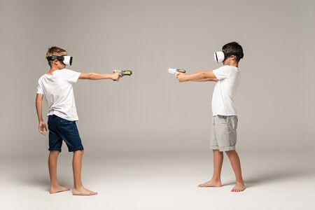 Photo pour full length view of two brothers in vr headsets aiming at each other with toy guns on grey background - image libre de droit
