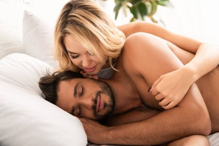 Photo for woman hugging her sleeping boyfriend in bed in the morning - Royalty Free Image